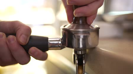 grãos de café : barista presses coffee in a horn.
