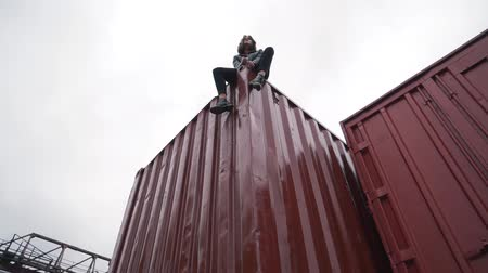 comprador : Fashion girl sits on a freight container.