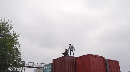 chock : Couple walk on a freight container.