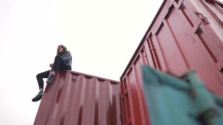 sáně : young girl sits on a freight container.