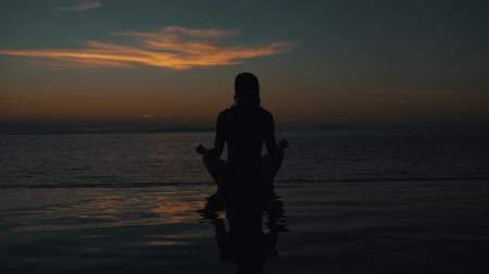 meditál : girl meditates at sunset by the ocean