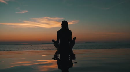 размышлять : girl meditates at sunset overlooking the ocean Стоковые видеозаписи