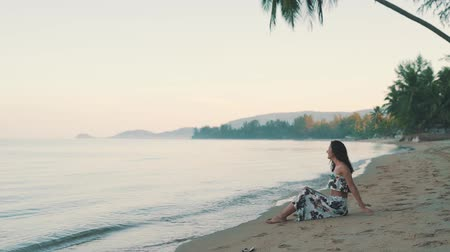 white sand : happy girl sitting on the sand by the ocean Stock Footage