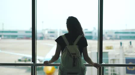 first class : girl standing at the window in the airport lounge Stock Footage