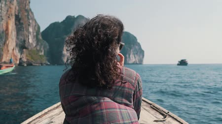 arch rock : girl rides a boat to the rocks in the ocean Stock Footage