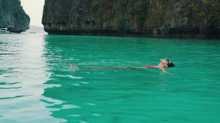 costa azzurra : girl swims in turquoise water in the bay