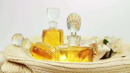 fragrances : Several vintage bottles of perfume with the glass stoppers on the old woven straw object