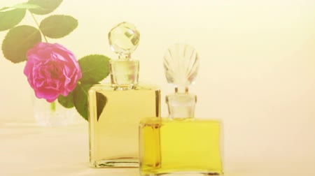 Two glass bottles of the perfumes and the flower Stok Video