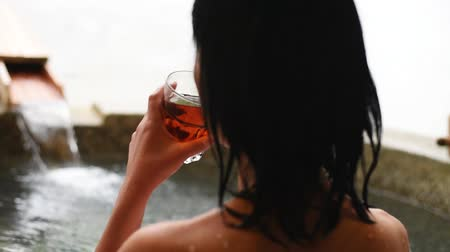 geotermální : rear view of asian mature woman hold a cup of tea at the hot spring pool Dostupné videozáznamy