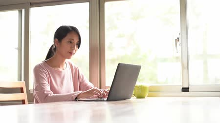 use computer : young asian woman working at home with laptop on wooden table