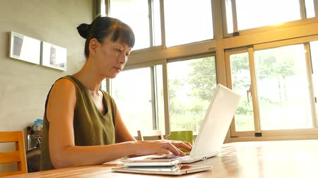 Asian mature woman using laptop, concept of working at home