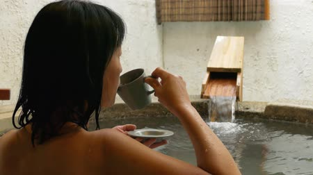 rear view of asian mature woman hold a cup of tea at the hot spring pool Stok Video