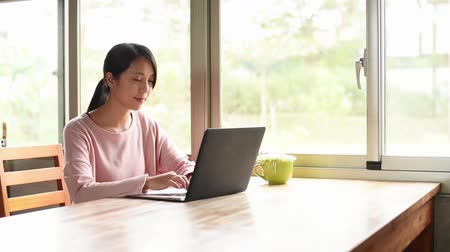 use laptop : young asian woman working at home with laptop on wooden table