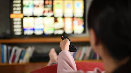 laying : woman watch tv at home and using the remote
