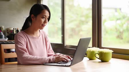 korejština : young asian woman working at home with laptop on wooden table