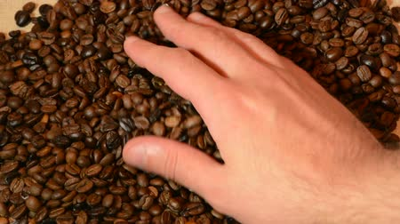 Man hand grab coffee beans and check quality. Male rolling, swirl and fall roasted coffee . Drink concept. Close up, selective focus