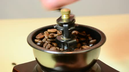 Roasted coffee beans grinding into mill. Prepare coffee on old and retro method. Close up, selective focus