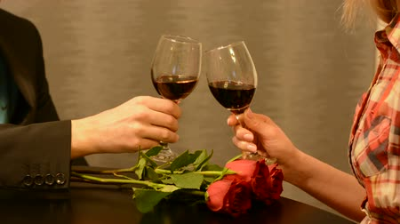 Man and female toasting with glasses of red wine on restaurant table with red rose flowers. Romantic dinner and Valentines Day concept. Close up, selective focus