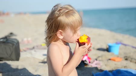 капелька : Child eats peach and water-melon on a beach