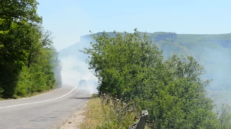 yanmış : Cars go through the smoke from a forest fire