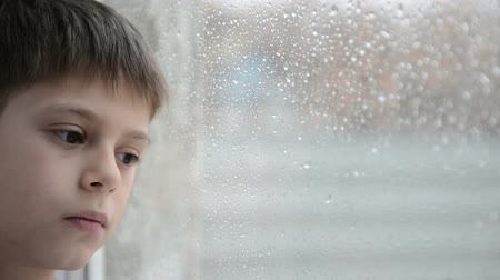 unott : Boy looks at rain in a window Stock mozgókép