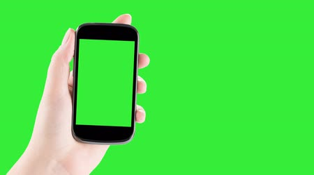 kezek : Holding Smartphone, Closeup of female hands using a smart phone. chroma key, green screen. 4K