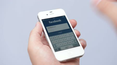 sosyal : SIMFEROPOL, RUSSIA - JULY 17, 2014:  Facebook Login page on an white Apple iPhone screen. Facebook is largest and most popular social networking site in the world. Stok Video