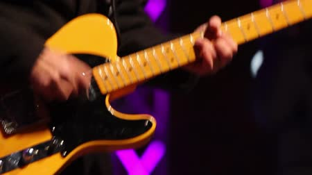 loud music : A guitarist playing his guitar on a stage at a concert Stock Footage