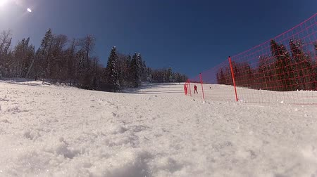 slalom : Low angle view of the skiing slope. One person is skiing downhill doing slalom and passes beside camera...