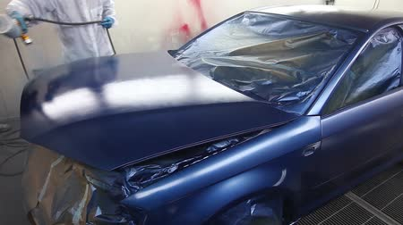 repaint : A car being painted in a painting chamber