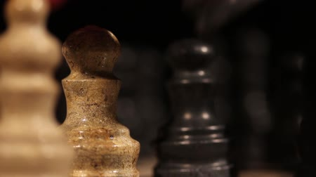 мозговая атака : Close up shot of a white pawn being attacked by a black knight in a chess game...