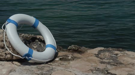 lifebelt : A white rescue buoy leaned on a stone near water...