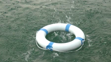 first aid kit : A white safe buoy being thrown into the water and floats on it...