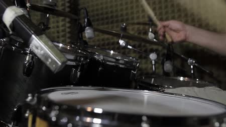 In a recording studio - a man playing on the drums...