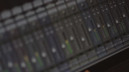 Footage of wave forms and audio mixers on a screen in a recording studio... Wideo