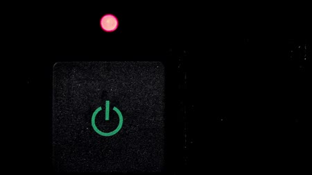 Footage of somebody pressing the on-off switch with a green-red lamp...