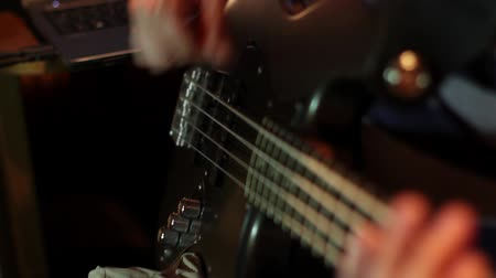 Close up footage of a musician playing on a bass guitar... Wideo