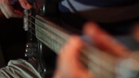 Close up footage of a person playing on a bass guitar... Wideo