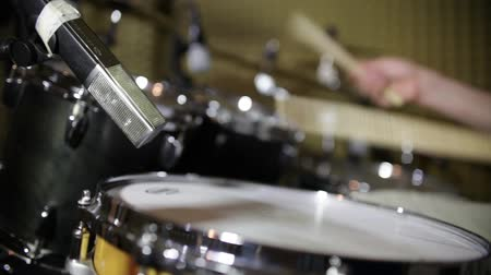 roll up : Low angle shot showing a person practicing drums in an isolated studio room...