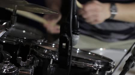 A man playing drums in a recording studio - the shot moves form the right to the left...