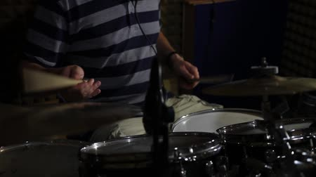 A man playing and practicing drums in a recording studio...