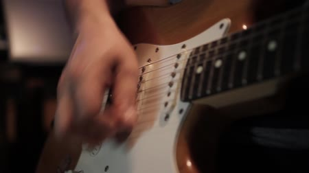 A musician playing on his elctric guitar - the shot moves from left to right...