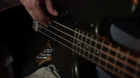 A man playing on his black bass guitar...