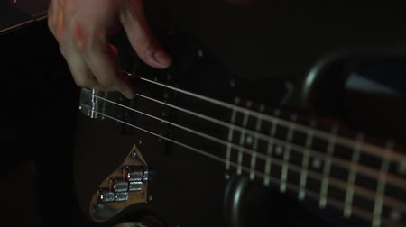 Footage of a man playing on his black bass guitar...