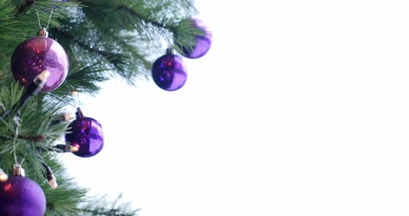Footage of a Christmas tree with purple and white balls on it...