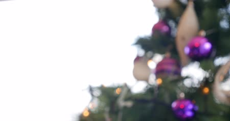 Footage of a Christmas tree with purple and white balls on it....