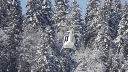 Footage of a winter scene and a helicopter going to a rescue mission to the mountains...