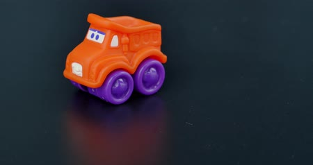 A small orange toy car on a gray background being pushed into focus... Wideo