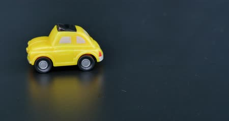 A small yellow car coming into frame from the right side...