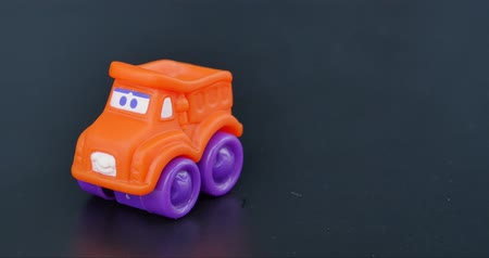 Footage of a small orange toy car on a gray background coming into frame...